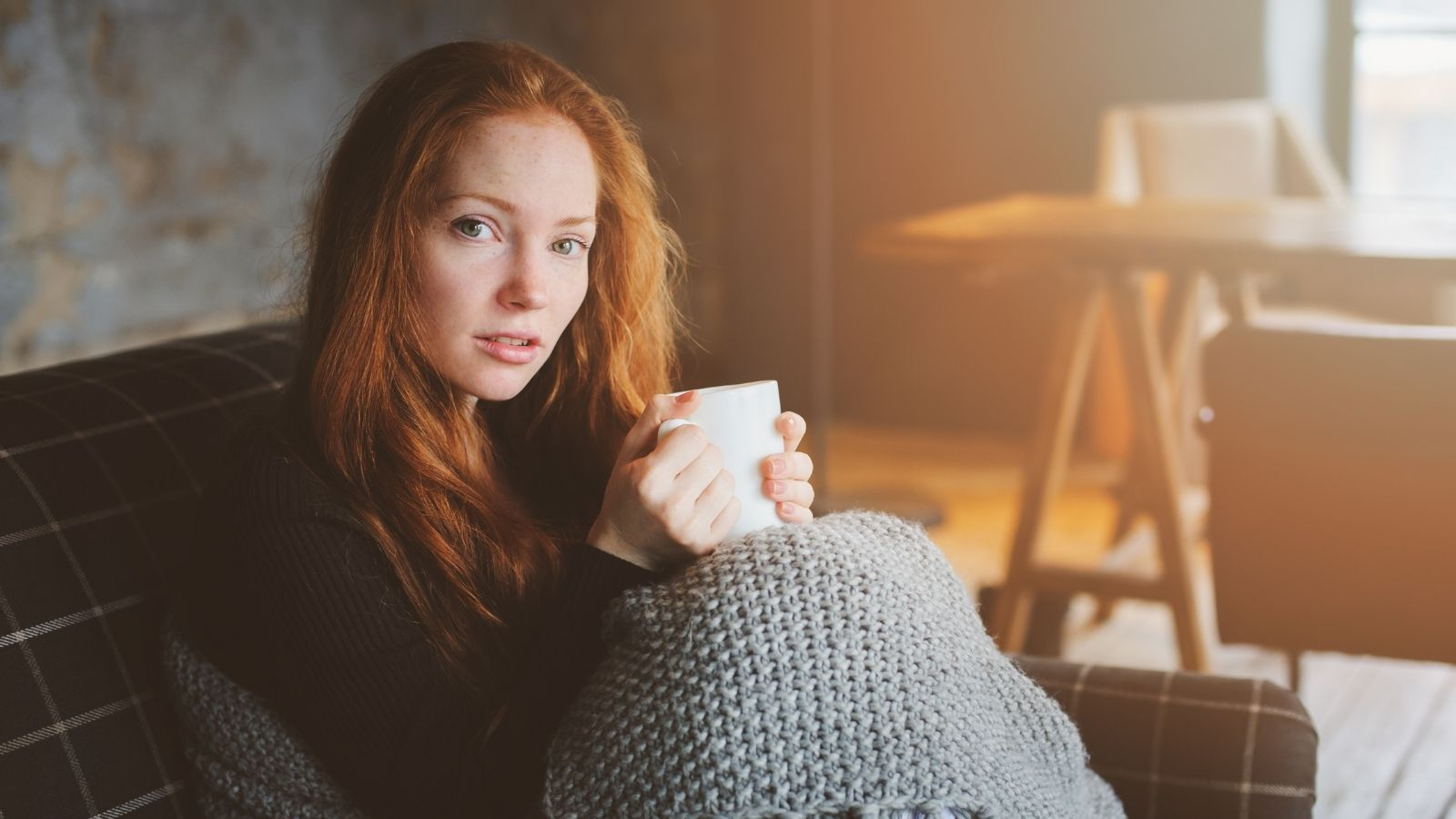 A sick woman drinks herbal tea while covered in a blanket.