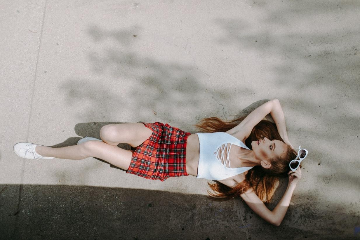 Woman in white halter top and red plaid skirt lying on concrete pavement