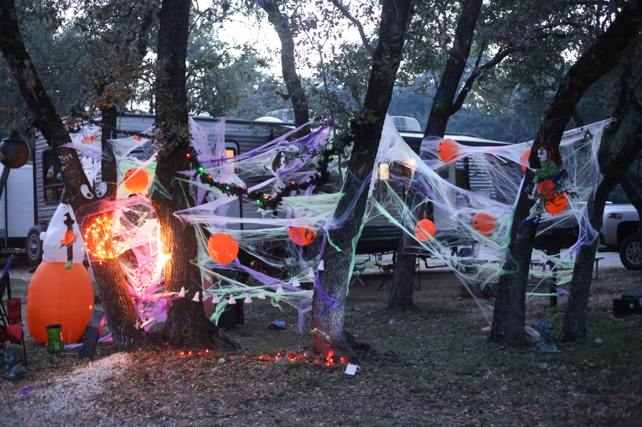 Campground with RV decorated for Halloween with spider webs and lights