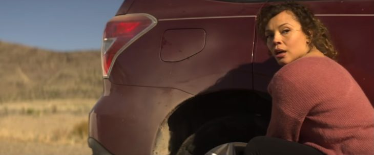 Mujer cambiando el neumático de un automóvil, escena de la película Rattlesnake, Netflix