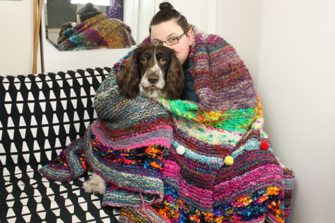 a women and a springer spaniel sat on a black and white sofa, wrapped in a multicoloured and multitexture blanket