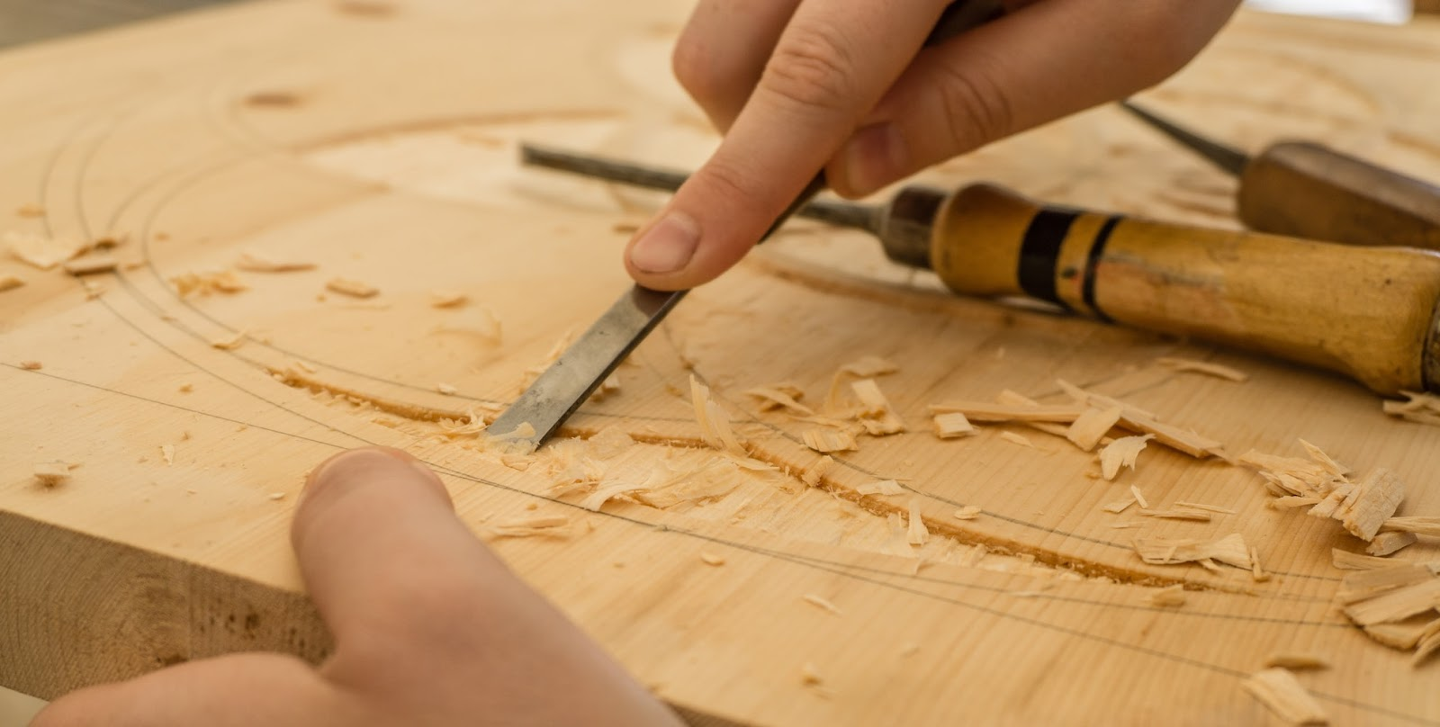 Carpenter carving shapes into wood