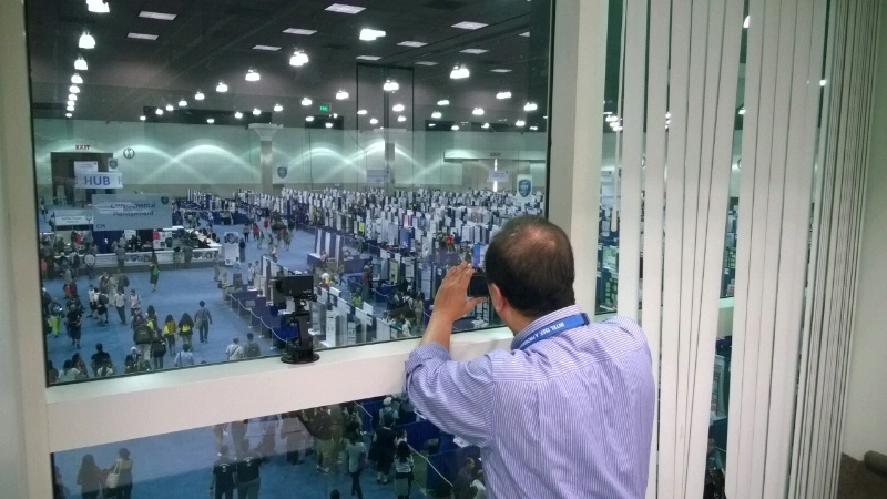 A man looks out of a window into a large room filled with science fair posters.