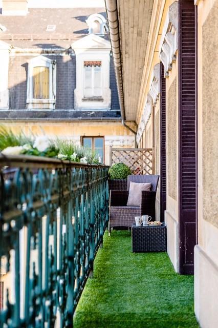 Искусственный травяной ковер и несколько плантаторов оконных коробок с небольшими цветами в них сделают ваш балкон небольшим городским садом.