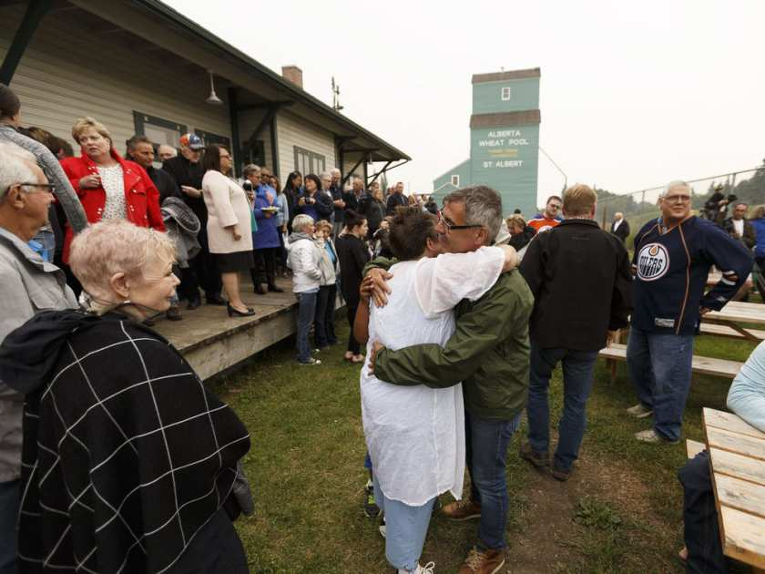 Daughter Stacey Worsfold (in white) hugs a supporter during a memorial for Ron Worsfold at the St. Albert Grain Elevator Park in St. Albert on Sunday, July 16, 2017. Worsfold was killed in a homicide.