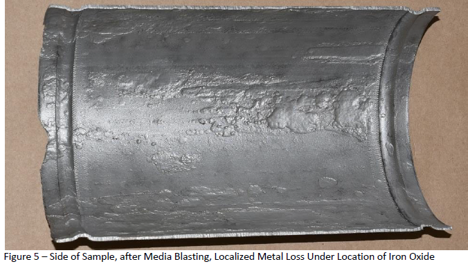 Side of sample after media blasting, localized metal loss under location of iron oxide