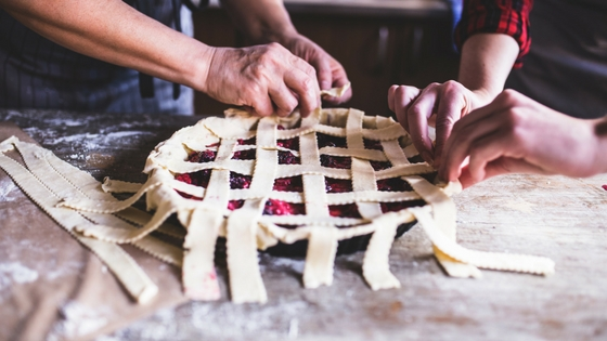 a berry pie at the stage where a lattice top is being added.