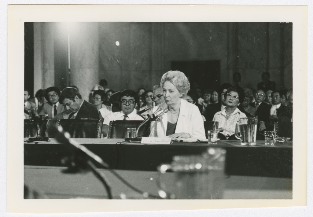 Lillian Baker seated alone at the witness table giving testimony. Behind her is an audience of mostly Japanese Americans.