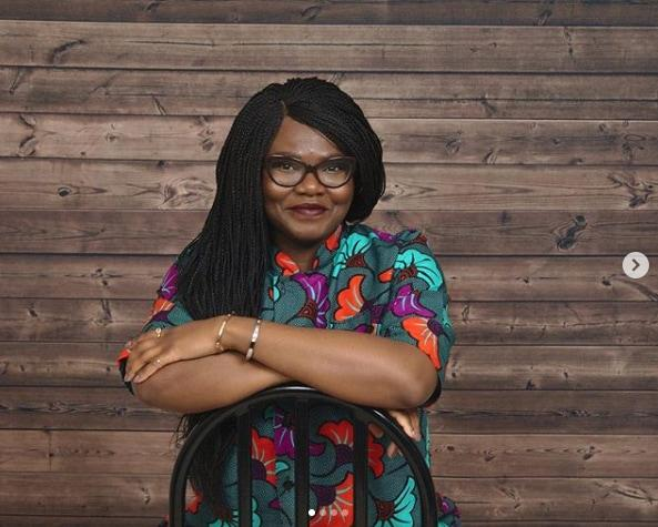 Nigerian food blogger Nma sitting in front of a rustic wood wall in a bright floral print shirt - Top 25 Social Media Influencers Making Impacts in Nigeria Today