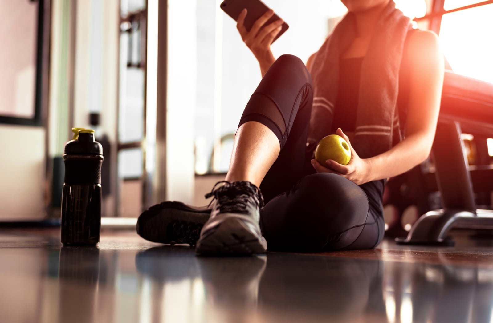 A woman checking her phone and eating an apple after working out