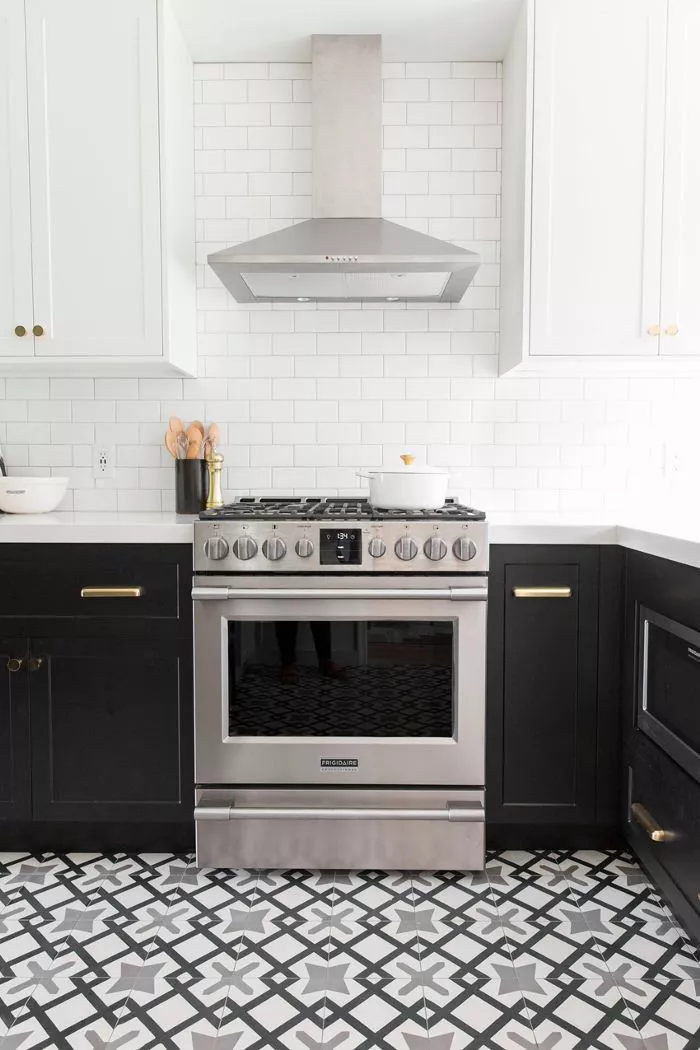 a two toned kitchen with black and white cabinets, stainless steel range hood, white backsplash and patterned tile floor