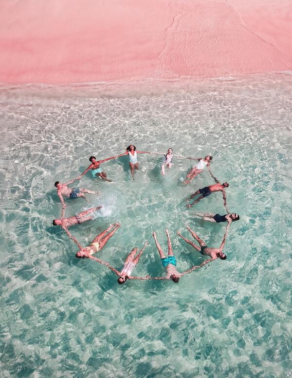 foto de cima de várias pessoas dando a mão em um círculo enquanto boiam no mar