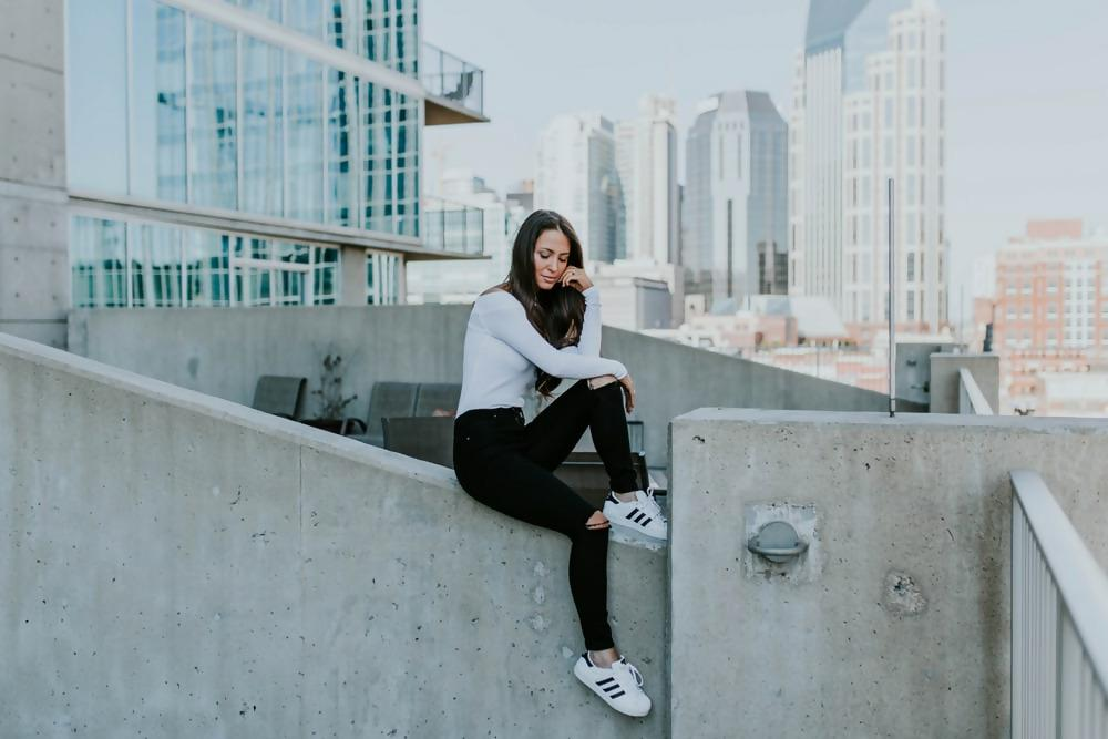 woman sitting on concrete building