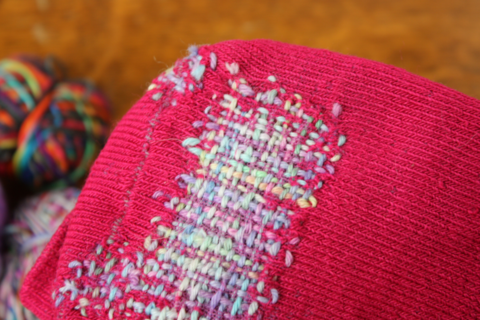 a close up of a pink sock with a large patch of pastel coloured darning