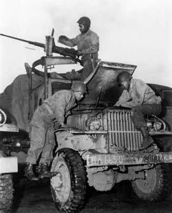 African American members of the World War II Red Ball Express repair a 2.5-ton truck while a crewman at a machine gun keeps watch for the enemy. Photo courtesy Army Transportation Museum.