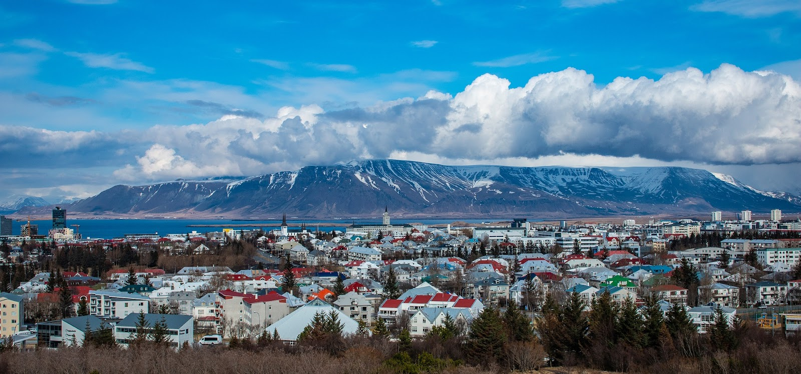 reykjavik iceland calm town skyline panoramic view from distance with large mountain and water in background on a sunny day