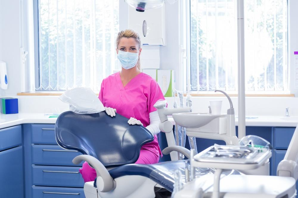 C:UsersstefaDownloadsPICTURESDentist in mask looking at camera beside chair at the dental clinic.jpeg
