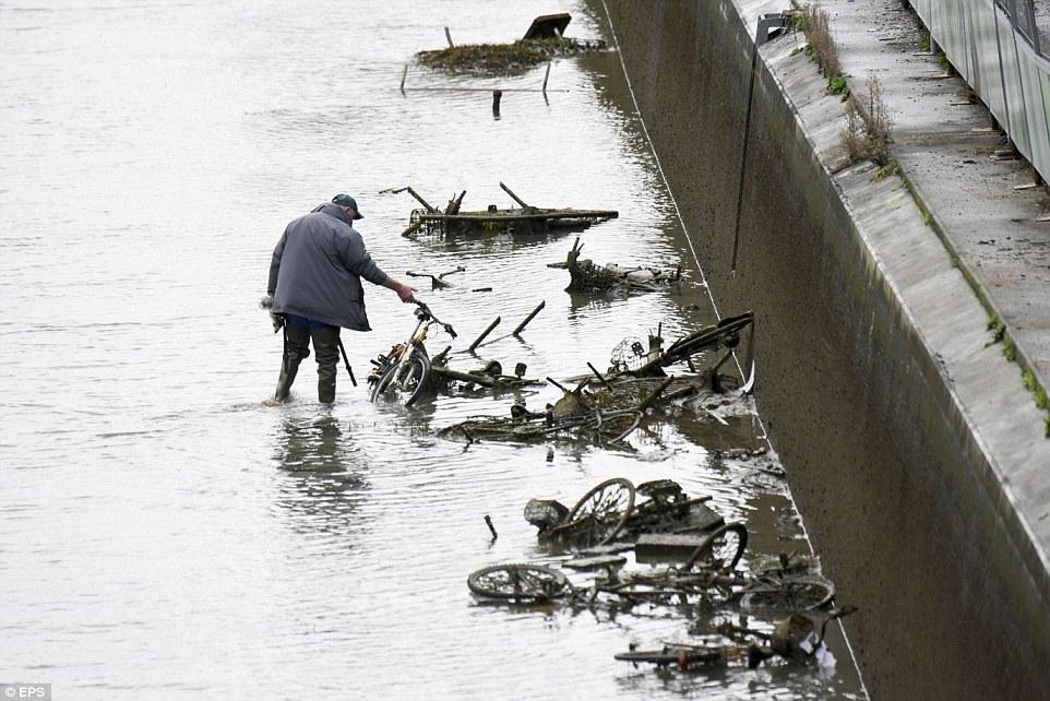 遺棄:一名男子在運河底部檢查了許多廢棄的自行車,這些自行車已經排放了15年