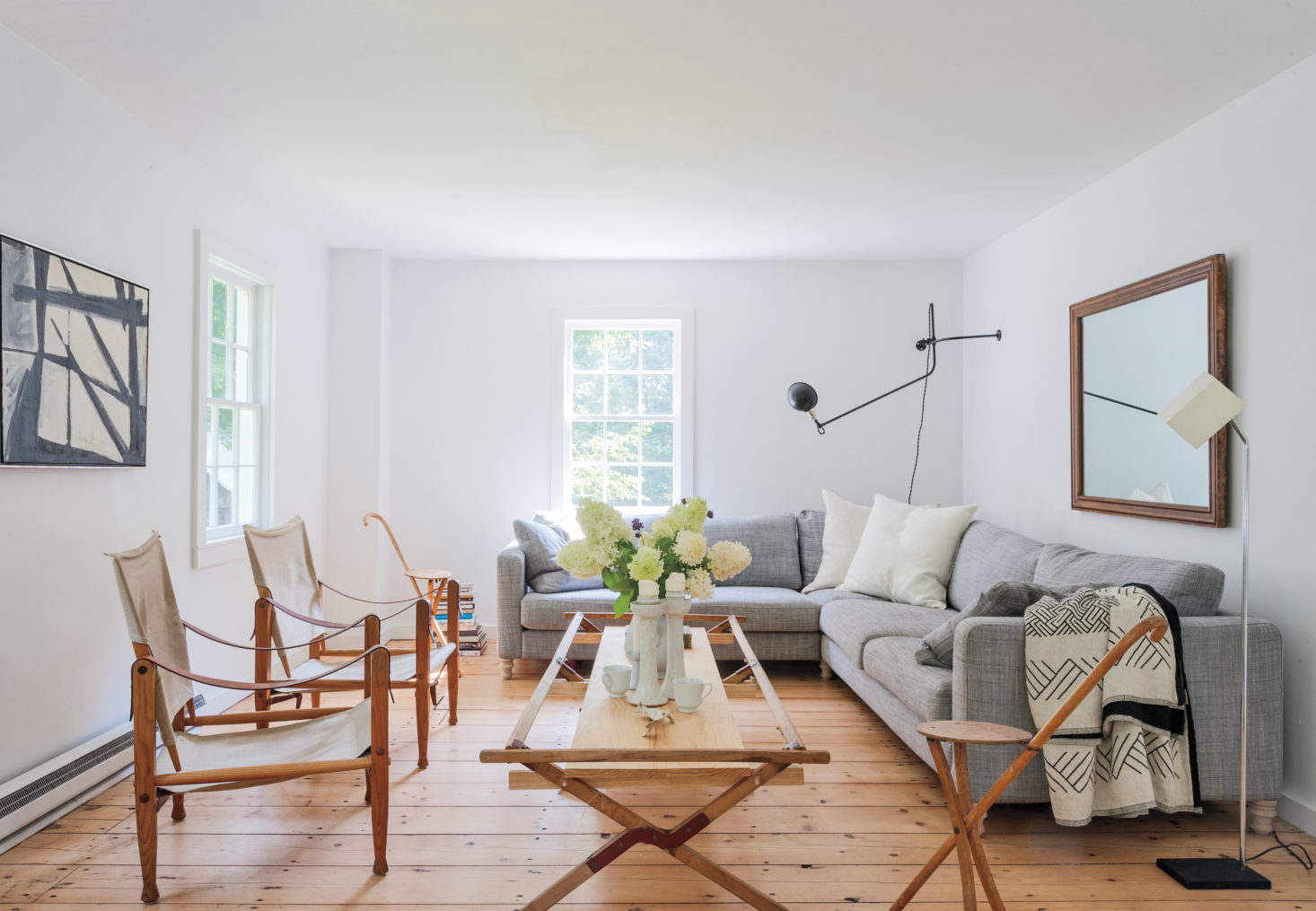 In their Hudson Valley living room, Robert Highsmith and Stefanie Brechbuehler of Workstead maximize a sense of space by using leggy, low-profile furniture and fixtures as well as a mirror over the couch. They also keep the space looking uncluttered by ditching the drapes and the rug.Photograph by Matthew Williams fromRemodelista: A Manual for the Considered Home.