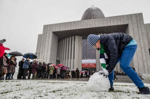 A young man makes a snowball as people queue to enter the Temple of Divine Providence before the opening ceremonies, on November 11, 2016.