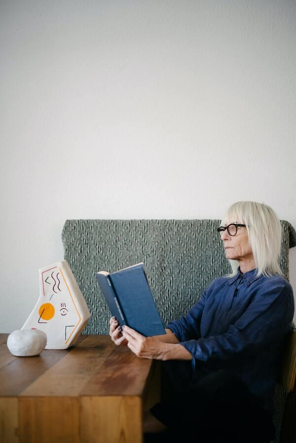 Foto de uma senhora sentada lendo um livro.
