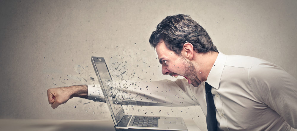 Man punching computer out of frustration.