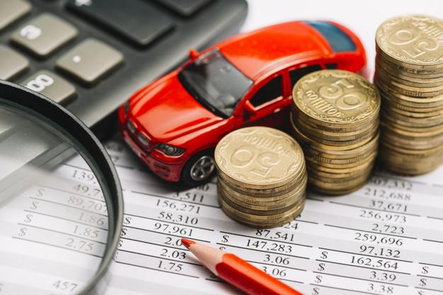 Car; stack of coins; colored pencil; calculator and magnifying glass on financial report Free Photo