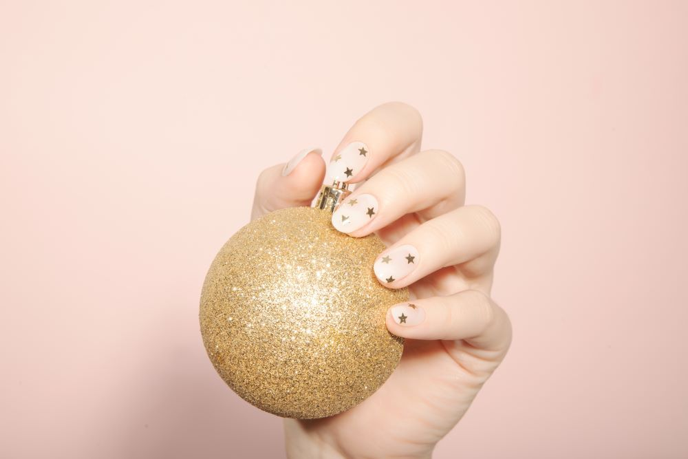 nude nails with tiny gold glitter stars