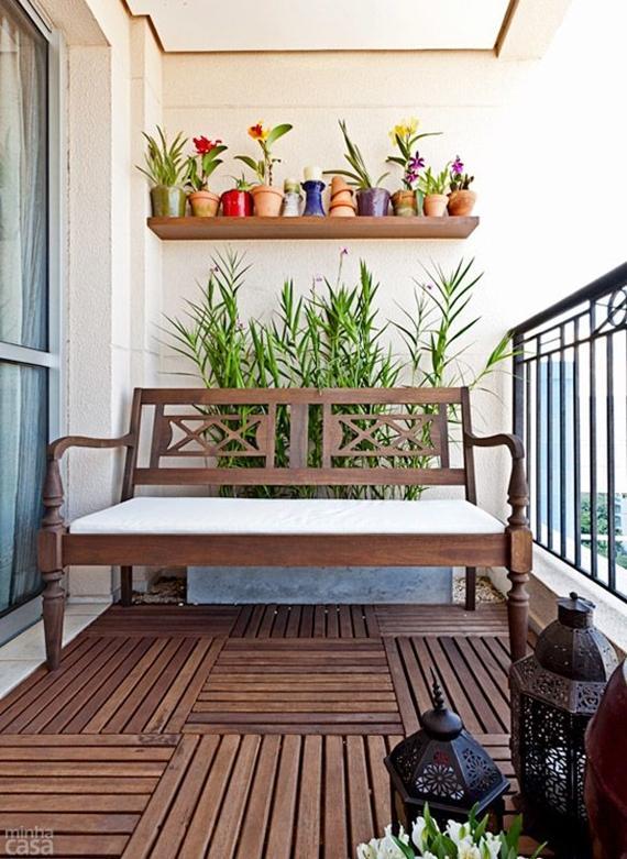 Varanda pequena com deck de madeira, sofá de madeira com estofado branco e prateleira de madeira com vasinhos coloridos de plantas.