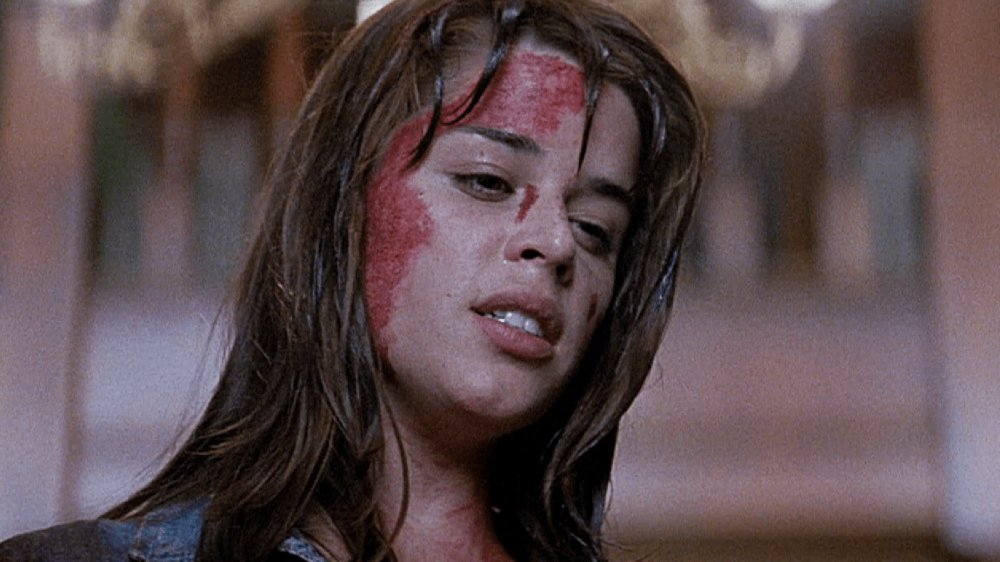Neve Campbell as Sidney Prescott in Scream (1996). A close up on Sidney, a teenage girl whose long brown hair is slick with blood which covers one side of her face. She is looking down, away from the camera, with an exhausted expression.