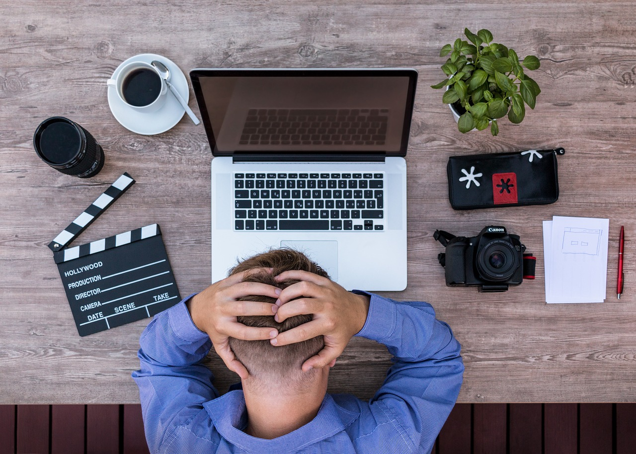 A man holding his head while in front of his laptop with a cup of coffee, a small plant, a camera, notepad and pen on the table, seems like having trouble concentrating.
