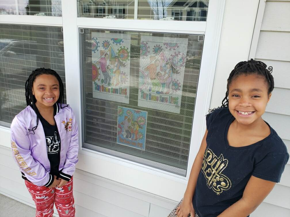 Two girls stand next to a window where their coloring pages are displayed.