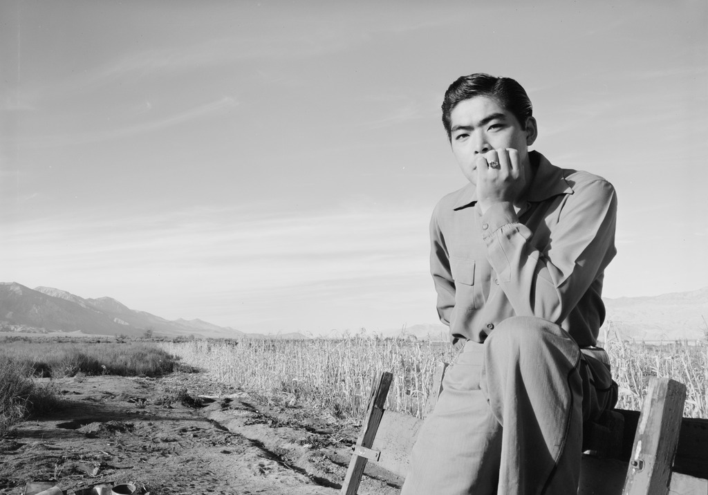 A young man leaning against a wooden fence in Manzanar. His arm is propped up on one of this legs and he is resting his chin on his hand with a pensive look.