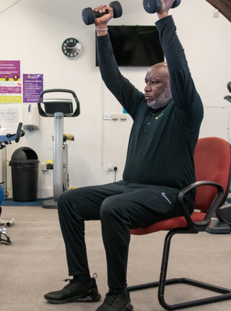 AB instructor Patrick seated in a chair with feet at hip width apart. He is holding a dumbell in each hand and his arms are stretched out above his shoulders