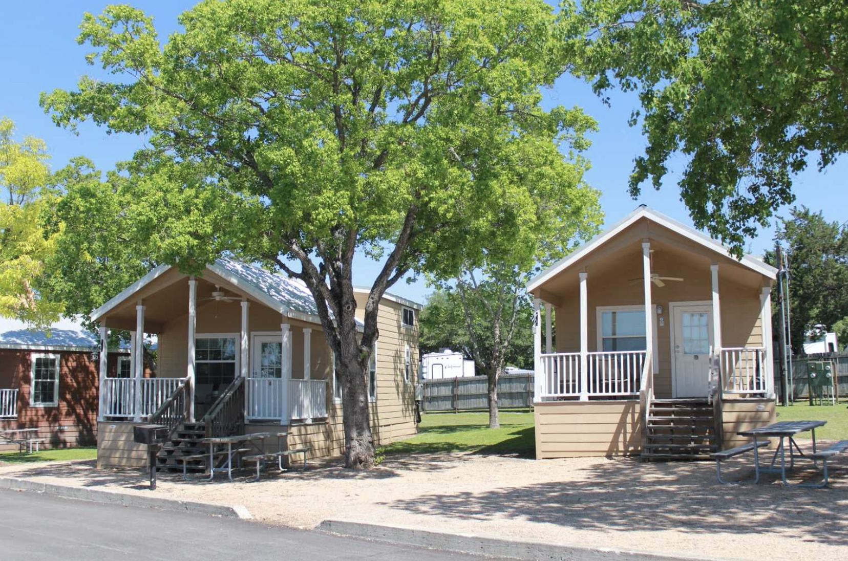 Cabins at Texas campground with trees and blu sky