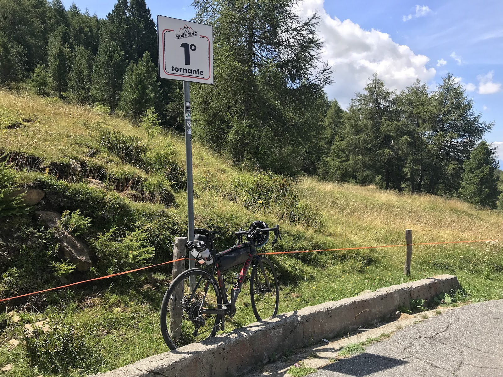 Passo del Mortirolo from Tovo - bike leaning against tornanti 1 sign.