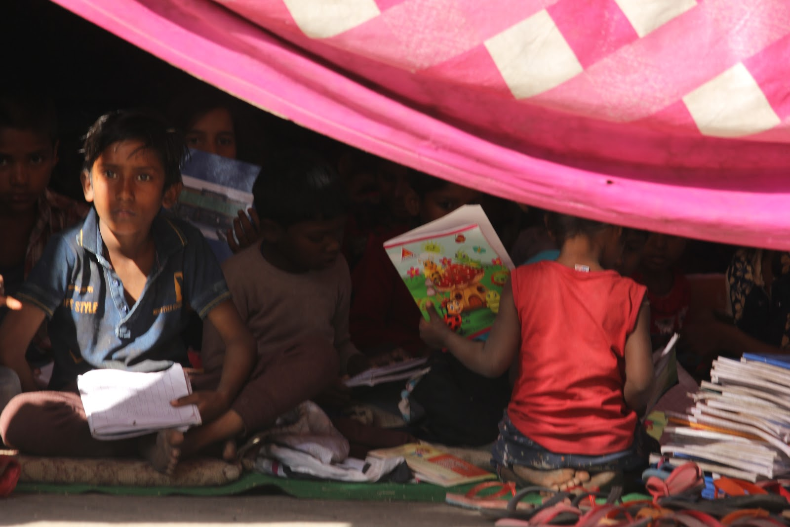 Children assemble in the tent as they wait for their class to begin.
