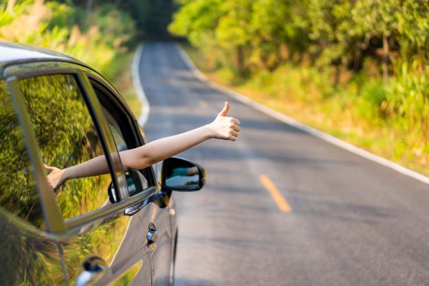 Mão feminina fazendo sinal positivo de dentro do carro, aprovando a ideia de melhores carros seminovos