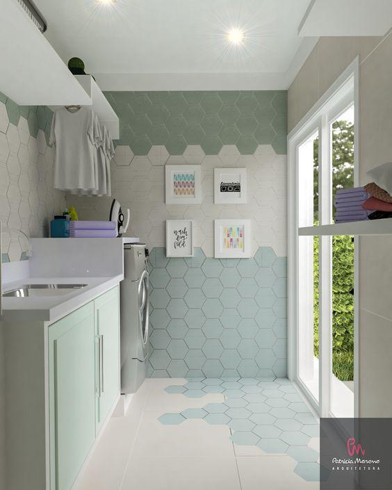 Area de serviço com revestimento hexagonal na parede em degrade verde e branco e meio piso com revestimento hexagonal e demais porcelanato branco, armários verde e branco e lavadora.