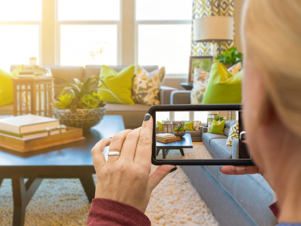 women photographing living room with smartphone