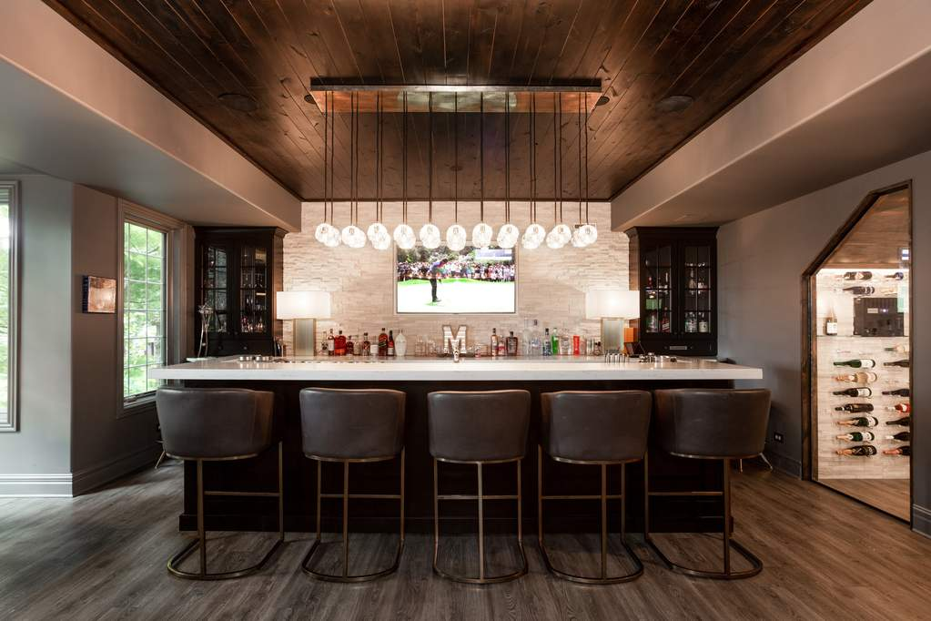 Basement par with multi-orb pendant light, dark wood base and white quartz countertops with a flagstone backdrop and leather bar stools.
