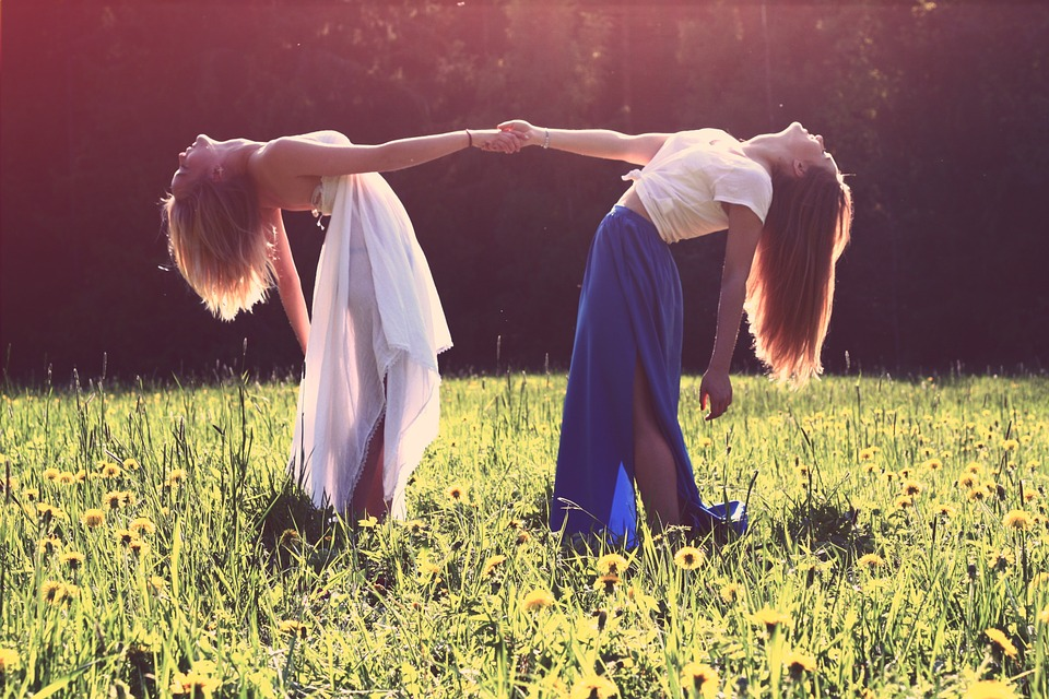 be there for your friends - 2 women holding hands in a field as if dancing