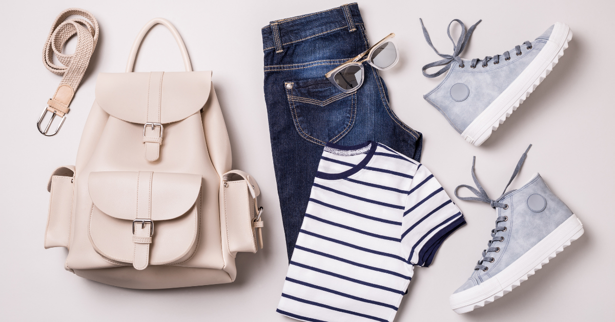 An outfit composed of a beige bag, jeans, a striped shirt, glasses and shoes.