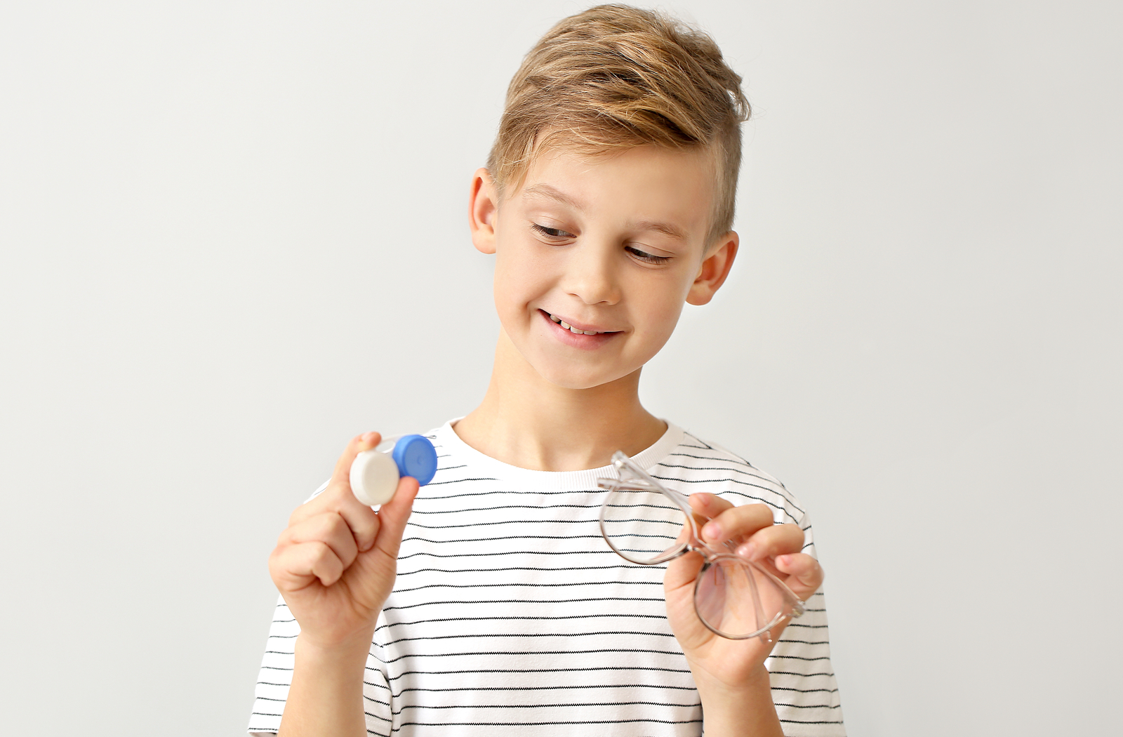 Child smiling and looking at the contact lenses he's holding next to glasses