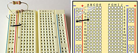 A breadboard with two resistors and a black wire.