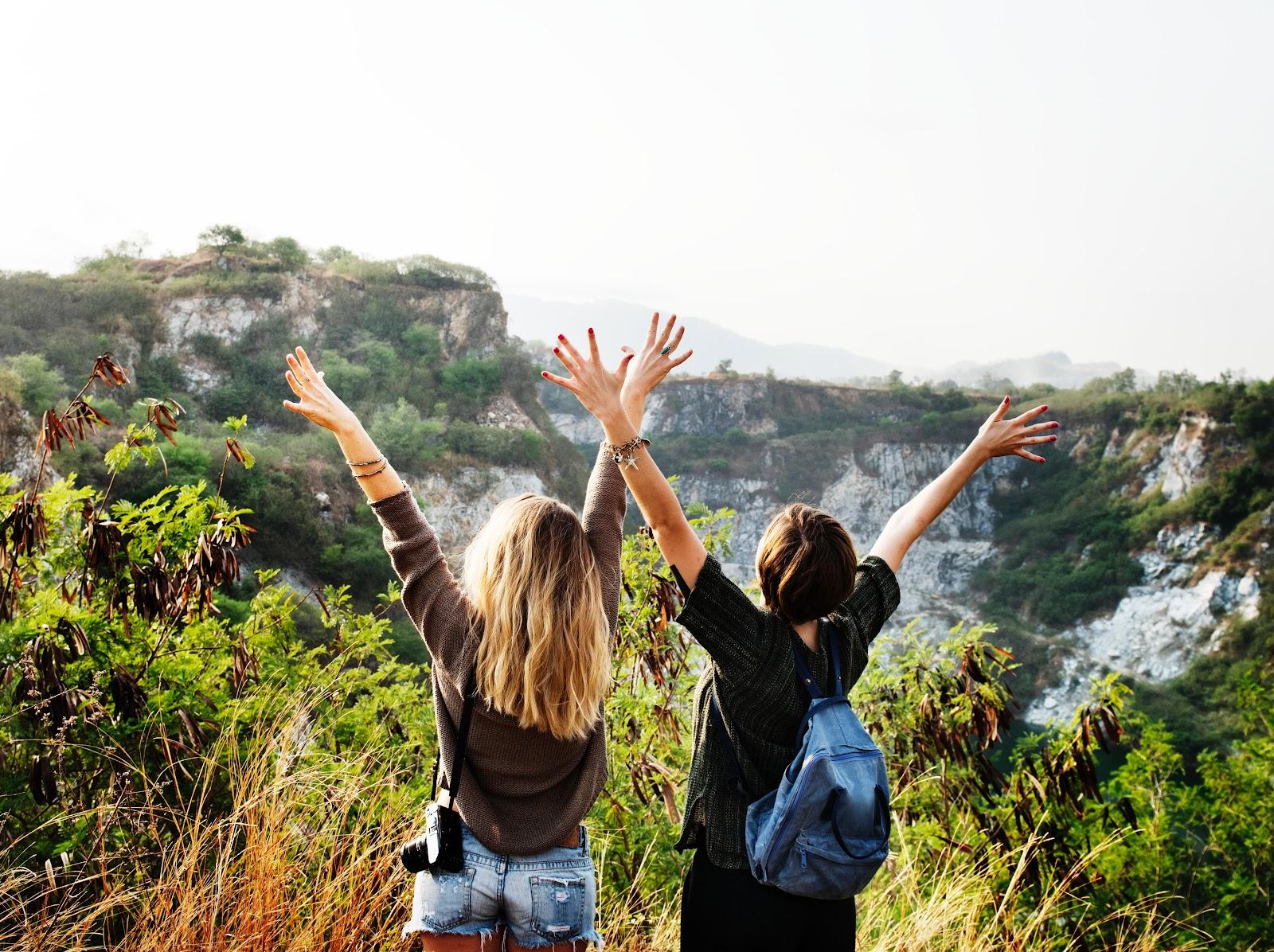 Doua fete fericite cu fata spre munti