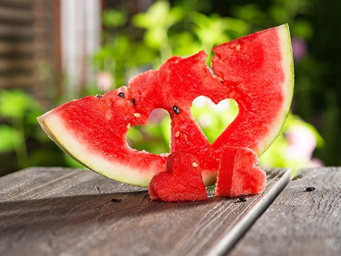 Ein Stück Wassermelone mit zwei ausgeschnittenen Herzen auf einem Tisch - die Frucht kann helfen, den Blutdruck zu senken.