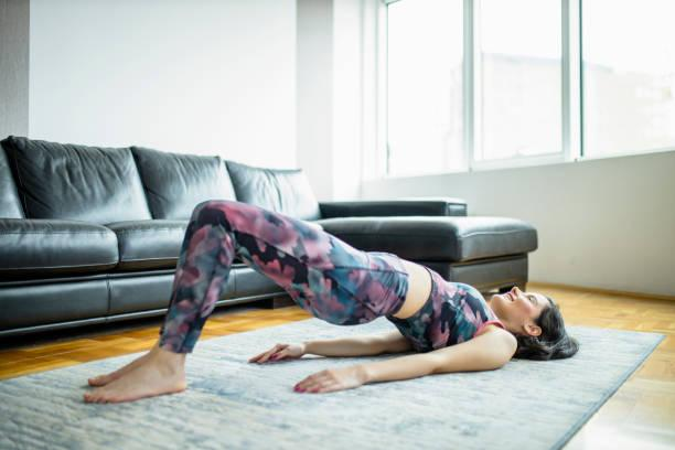 Woman practicing yoga, doing Glute Bridge exercise, dvi pada pithasana at home Woman practicing yoga, doing Glute Bridge exercise, dvi pada pithasana at home bridge stock pictures, royalty-free photos & images