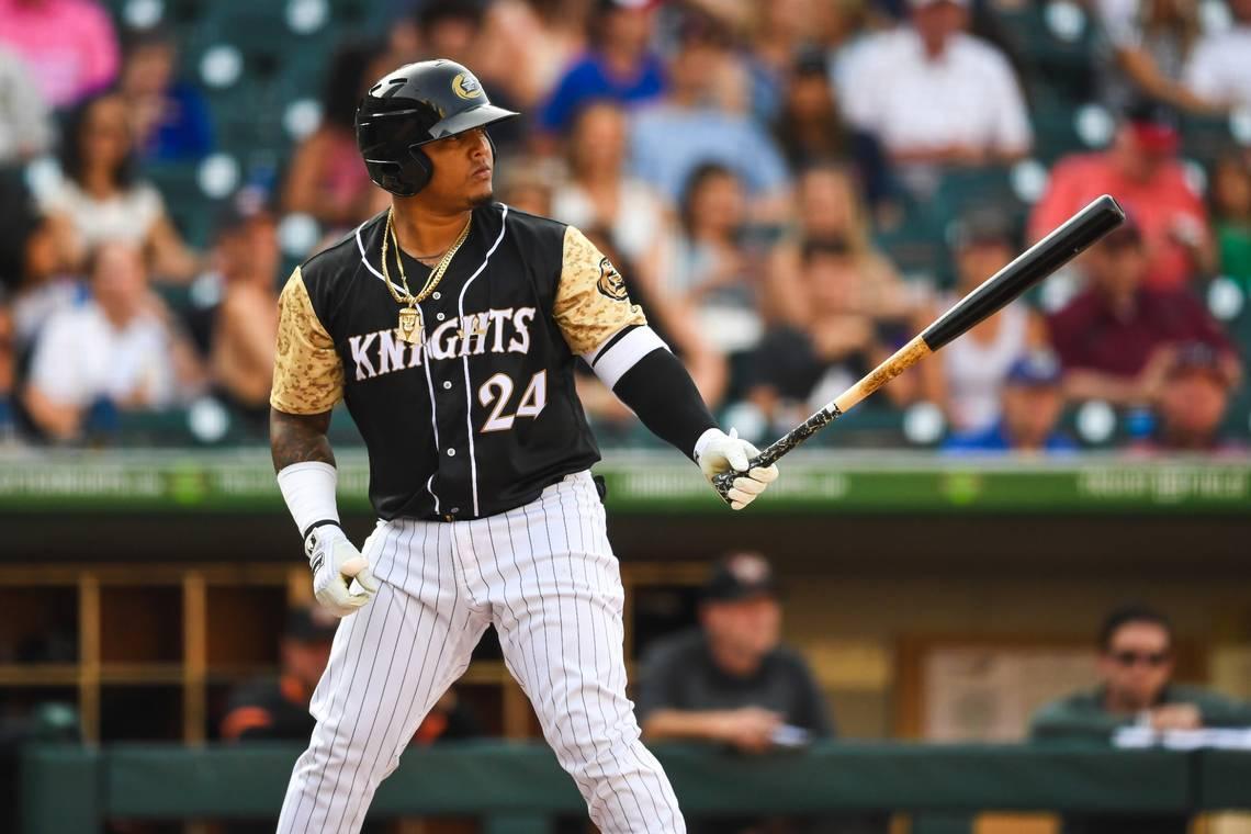 Un jugador de béisbol con un bate de béisbol  Descripción generada automáticamente