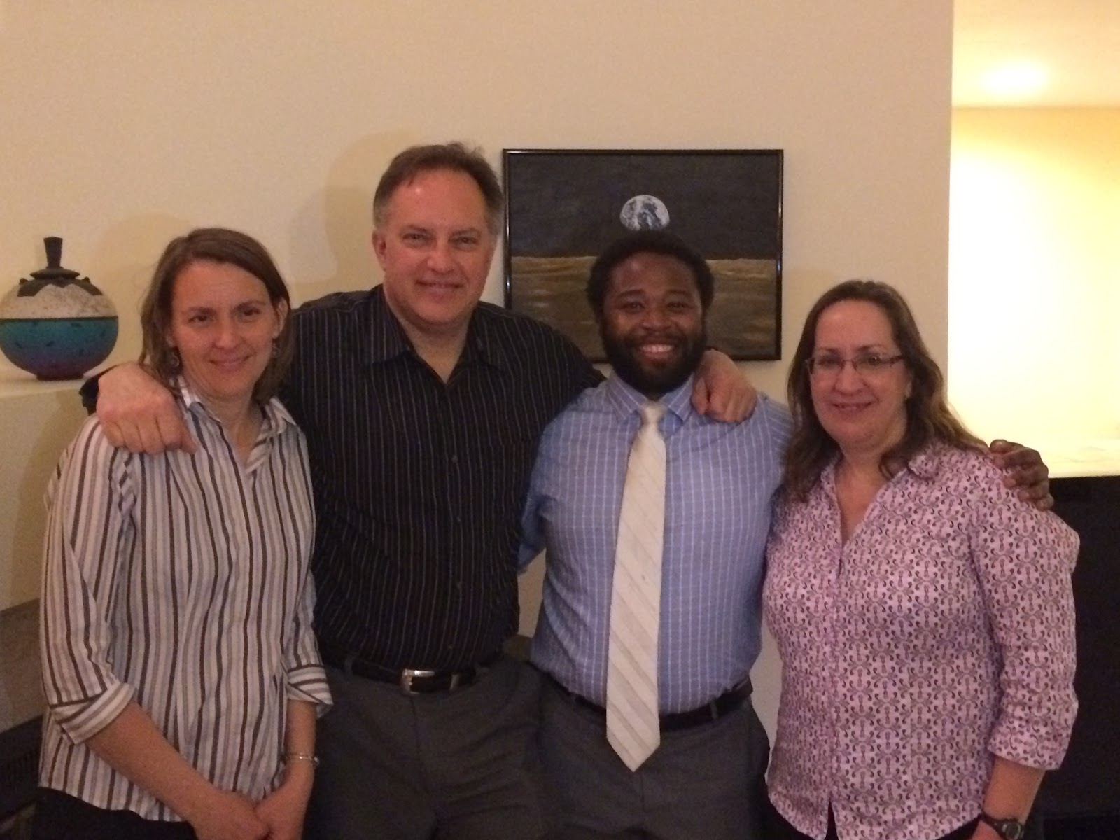 Dr. Mosby and his three advisors posing together happily.